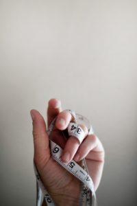 main avec un mètre ruban parallèle avec la mesure nécessaire à l'évaluation